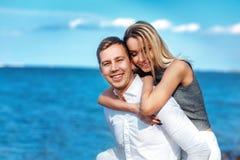 Lyckliga par på havsbakgrund förälskade lyckliga unga romantiska par har gyckel på l strand på den härliga sommardagen Arkivfoton