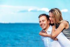 Lyckliga par på havsbakgrund förälskade lyckliga unga romantiska par har gyckel på l strand på den härliga sommardagen Royaltyfria Foton