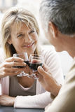 Lyckliga par på kafét som rostar vinexponeringsglas Arkivfoto