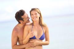 Lyckliga par på omfamna för strand Royaltyfri Bild