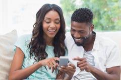 Lyckliga par på soffan genom att använda telefonen Arkivfoton