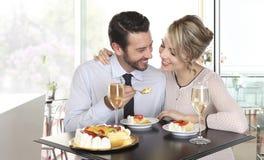 Lyckliga par på stången med champagne och frukt bakar ihop, älskar Royaltyfria Bilder
