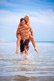 Lyckliga par på stranden royaltyfria bilder