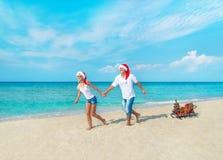 Lyckliga par på stranden i röda santa hattar med gåvor, släden och december Royaltyfri Foto
