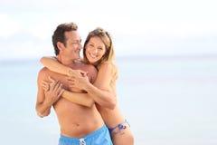 Lyckliga par på stranden som har gyckel Arkivfoton
