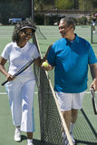 Lyckliga par på tennisbanan Fotografering för Bildbyråer