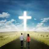 Lyckliga par på vägen med ett kors Arkivfoton