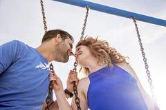 Lyckliga par på gungor i sommar Royaltyfri Fotografi
