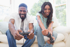 Lyckliga par på soffan som spelar videospel Arkivfoto