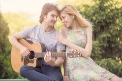 Lyckliga par, pojkvän som spelar gitarren för hans flickvän Fotografering för Bildbyråer