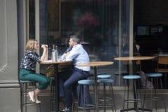 Lyckliga par sitter på tabellen i gatakafé nära stadmarknad Arkivfoton