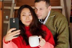 Lyckliga par sitter på trappabakgrunden av den nya lägenheten arkivfoton