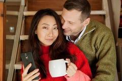 Lyckliga par sitter på trappabakgrunden av den nya lägenheten arkivbild