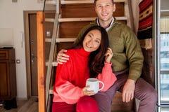 Lyckliga par sitter på trappabakgrunden av den nya lägenheten royaltyfri fotografi