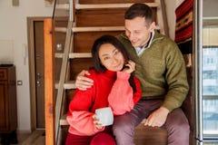 Lyckliga par sitter på trappabakgrunden av den nya lägenheten royaltyfria foton