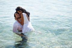 Lyckliga par skriver in i vatten i kläder, har roliga ögonblick, kopieringsutrymme arkivbilder