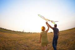 Lyckliga par som är förälskade med att flyga en drake Arkivbild