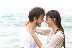 Lyckliga par som är klara att kyssa att bada på stranden royaltyfri fotografi