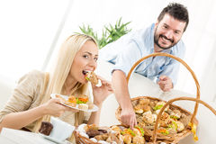 Lyckliga par som äter bakelse Fotografering för Bildbyråer