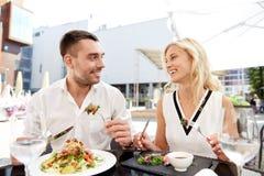 Lyckliga par som äter matställen på restaurangterrassen Fotografering för Bildbyråer
