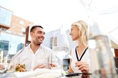 Lyckliga par som äter matställen på restaurangterrassen arkivbilder