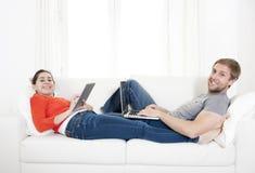 Lyckliga par som arbetar på deras bärbar dator och minnestavlor på en soffa Fotografering för Bildbyråer