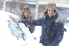 Lyckliga par som av borstar snö från bilen arkivbilder