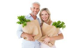 Lyckliga par som bär pappers- livsmedelsbutikpåsar Arkivbild