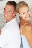 Lyckliga par som baksidt sitter för att bak Royaltyfri Foto
