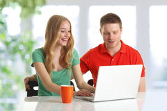 Lyckliga par som bläddrar på datoren Arkivbild