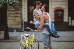 Lyckliga par som cyklar i staden Arkivbild