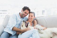 Lyckliga par som daltar deras gula labrador på soffan Fotografering för Bildbyråer
