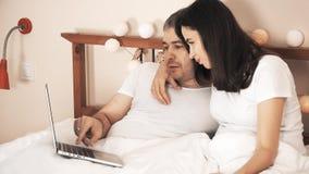 Lyckliga par som direktanslutet väljer gods och shoppar genom att använda deras bärbar dator i säng arkivfilmer
