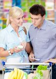 Lyckliga par som diskuterar shoppinglistan och de valda produkterna Arkivfoton