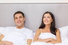 Lyckliga par som drömmer i säng Arkivbilder