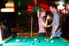 Lyckliga par som dricker öl och spelar snooker royaltyfri bild