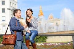 Lyckliga par som dricker kaffe som talar i Barcelona Arkivfoton
