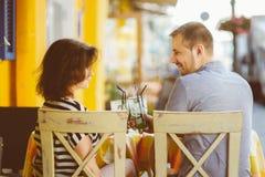 Lyckliga par som dricker lemonad eller mojito i Arkivbild