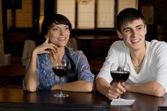 Lyckliga par som dricker rött vin på stången royaltyfri fotografi