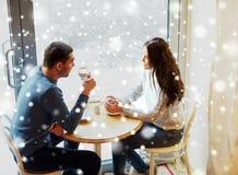 Lyckliga par som dricker te och kaffe på kafét royaltyfria bilder