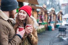 Lyckliga par som dricker varma drycker på jul, marknadsför Royaltyfri Bild