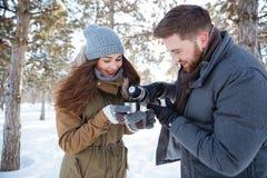 Lyckliga par som dricker varmt te i vinter, parkerar Royaltyfri Foto
