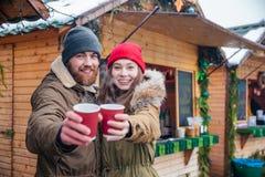 Lyckliga par som erbjuder varma drinkar till dig på jul, marknadsför Arkivfoto