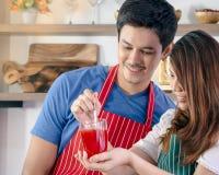 Lyckliga par som förbereder den sunda drinken arkivfoto