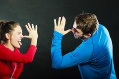Lyckliga par som förlöjligar ha gyckel som spelar dumbommen Fotografering för Bildbyråer