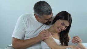 Lyckliga par som flörtar och att sitta på hemmastadd säng och att spendera tid tillsammans, affektion stock video