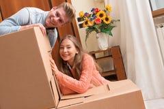 Lyckliga par som flyttar sig till det nya huset Royaltyfri Foto