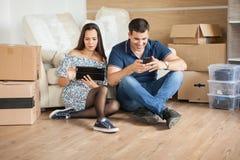 Lyckliga par som flyttar sig till ett nytt hem royaltyfri foto