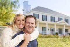 Lyckliga par som framme kramar av hus Royaltyfri Fotografi