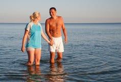 Lyckliga par som går på stranden Royaltyfri Bild